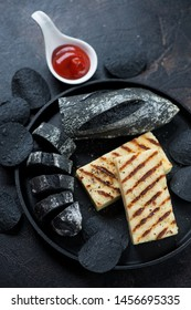 Round metal serving tray with grilled cheese, black baguette and black potato chips, elevated view, studio shot