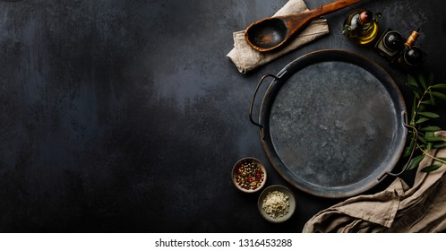 Round metal Tray and Spices on dark concrete backdrop Surface copy space for design text