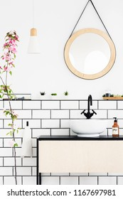 Round mirror above washbasin in white bathroom interior with pink flowers. Real photo