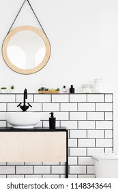 Round mirror above white cabinet in simple bathroom interior. Real photo
