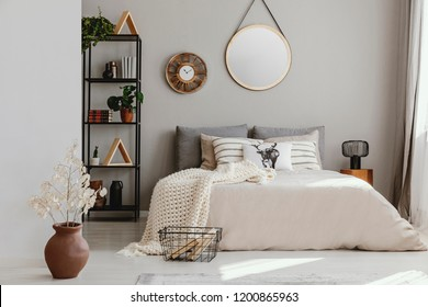 Round mirror and clock above bed with pillows in bright bedroom interior with flowers. Real photo