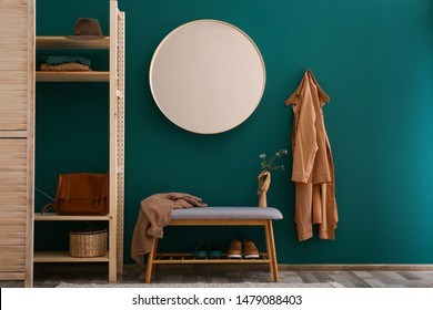 Round mirror on green wall in stylish hallway interior