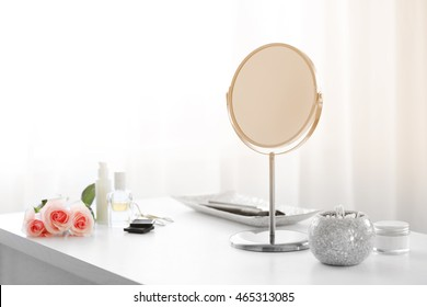 Round mirror on white dressing table