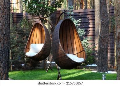 Round modern furniture plastic wicker chairs in garden
