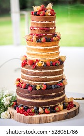 Round multi tiered wedding cake with sponge, cream, jam and fruit on a circular tree bark base