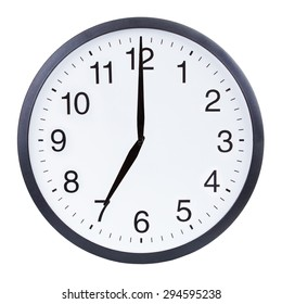 Round office clock showing seven o'clock isolated on white background