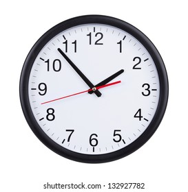 Round office clock shows five minutes to two