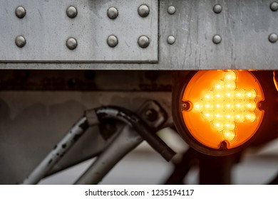 Round orange marker lights signal with turn on arrow on the side of aluminum big rig semi trailer show maneuvers of the trailer on the road warning other road traffic users
