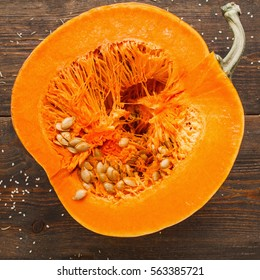 Round orange pumpkin half in cut. Close-up of fresh squash cutaway, ready for preparing. Seasonal fruit, healthy eating, nutrition concept