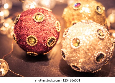 Round ornaments covered in rich jewels and glitter, baubles and soft lights for Christmas holiday, split tone
