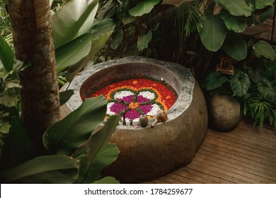 Round outdoor bath with tropical flowers. Luxury round bath outdoor in garden, bali style spa center. Round outdoor bathroom with flower in luxury chic and spa hotel in Bali in Ubud