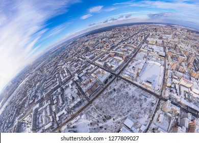 Round panorama aerial view on a winter city under a blue sky with white clouds: rows of streets with high-rise buildings and roofs under snow, a park, trees and a stadium with a football field.