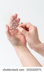 Round patches for acne and wrinkles on the hands on a white background. Acne and wrinkle patches for facial rejuvenation. Facial cleansing cosmetology.