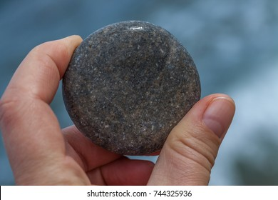 a round pebble hold in a hand with blue background