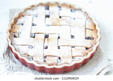 Round pie (linzer torte) in a red baking dish on light backround