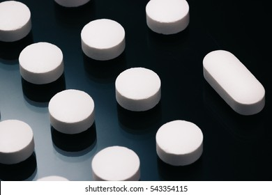 Round pills contrasted with an odd shaped tablet pill on a dark reflective surface