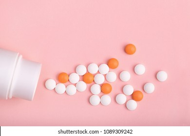 round pills of white and orange color poured out on a pink background of white plastic pill bottle.  top view. medicinal drug. biohacking concept