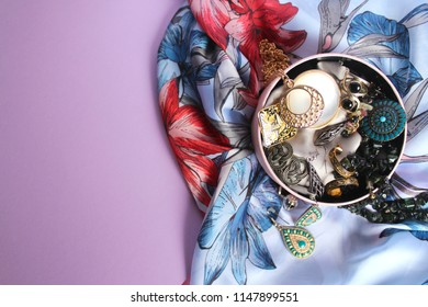 A round pink jewellery box with bijouterie: rings, pendants, bracelets, earrings, chains, on a light blue silk scarf with flowers and a light purple background. Beauty and fashion concept