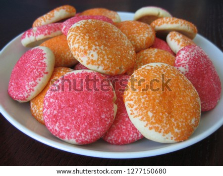 Round plate full of brightly-colored sugar cookies