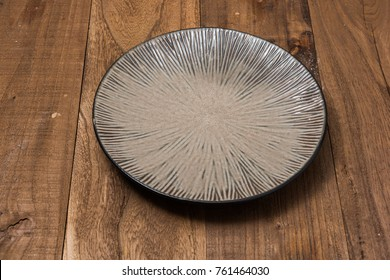 Round Plate on brown wooden table background side view