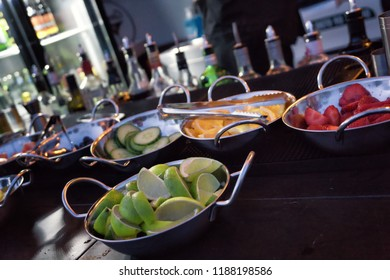Round plates with fruits like lime and orange slices to make cocktails.