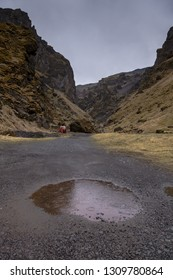 Round puddle and rain on a stony rocky mountain landscape of Iceland.