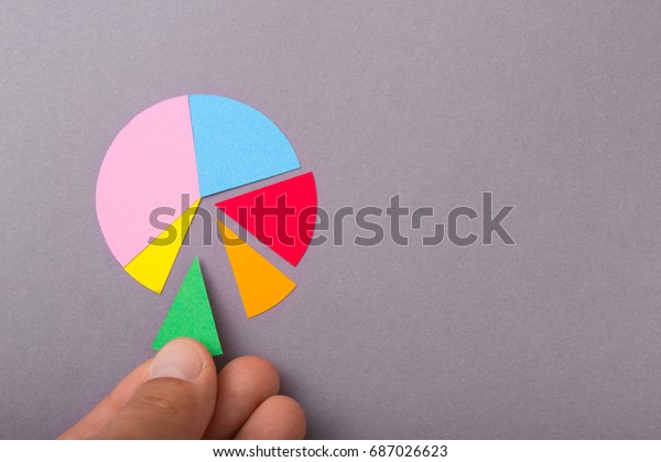 Round radial diagram with colored parts in the hands of a man on a gray background. Copy space for text