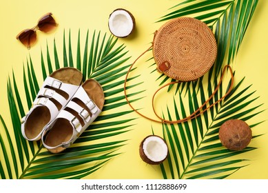 Round rattan bag, coconut, birkenstocks, palm branches, sunglasses on yellow background. Banner. Top view with copy space. Trendy bamboo bag and shoes. Summer fashion flat lay. Trip, vacation concept.