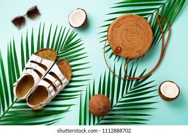 Round rattan bag, coconut, birkenstocks, palm branches, sunglasses on blue background. Banner. Top view with copy space. Trendy bamboo bag and shoes. Summer fashion flat lay. Trip, vacation concept.