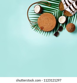 Round rattan bag, coconut, birkenstocks, palm branches, sunglasses on blue background. Square crop. Top view, copy space. Trendy bamboo bag and shoes. Summer fashion flat lay. Trip, vacation concept.