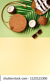 Round rattan bag, coconut, birkenstocks, palm branches, sunglasses on green background. Banner. Top view with copy space. Trendy bamboo bag and shoes. Summer fashion flat lay. Trip, vacation concept.