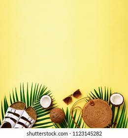 Round rattan bag, coconut, birkenstocks, palm branches, sunglasses on yellow background. Square crop. Top view, copy space. Trendy bamboo bag and shoes. Summer fashion flat lay. Trip concept.