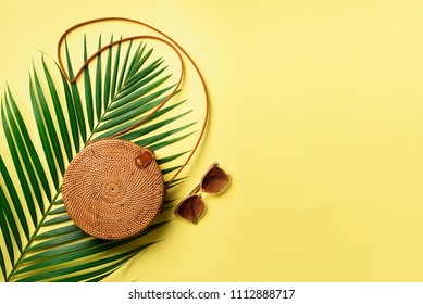Round rattan bag, sunglasses on yellow background. Banner. Top view with copy space. Trendy bamboo bag and white shoes. Summer fashion flat lay. Trip, vacation concept.