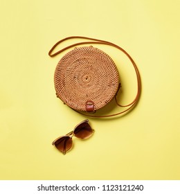 Round rattan bag, sunglasses on yellow background. Square crop. Top view with copy space. Trendy bamboo bag and white shoes. Summer fashion flat lay. Trip, vacation concept.