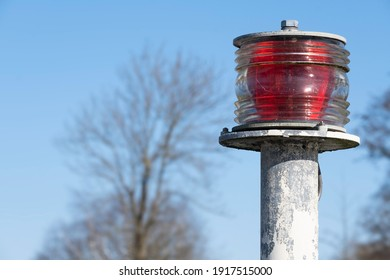 Round red beacon strobe light located at a pier by the sea mounted on top of a metal pole