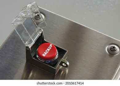 """Round, red button with safety hood raised. The button is located on a metal box and is ready to use. The button has the inscription """"backup"""". Close-up. Copy space."""
