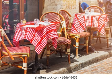 Round red tables with chairs of traditional outdoor French cafe in Paris, rue Mouffetard