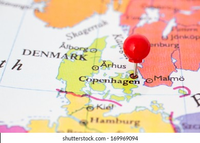 Round red thumb tack pinched through Copenhagen on Denmark map. Part of collection covering all major capitals of Europe.