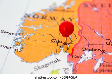 Round red thumb tack pinched through city of Oslo on Norway map. Part of collection covering all major capitals of Europe.