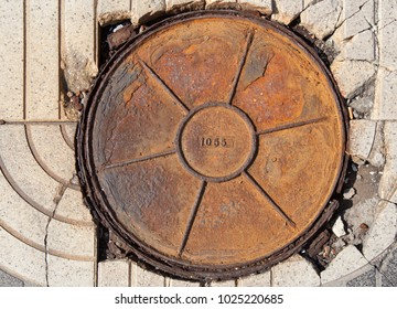 round rusty manhole cover number 1055, sunny