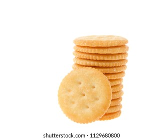 Round salted crackers stacked with one cracker in front isolated on white