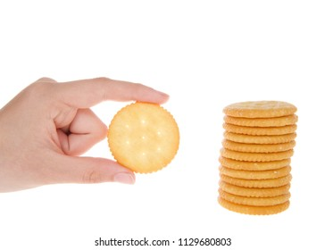 Round salted crackers stacked with young caucasian hand holding a single cracker next to pile.