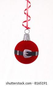 Round Santa Claus ornament  hung from a red a ribbon on a white background.