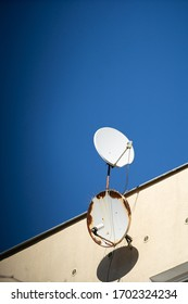 Round satellite dishes are receivers of electromagnetic waves transmitted by various television networks.