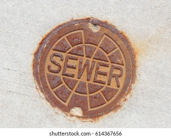 round sewer access cover set in concrete