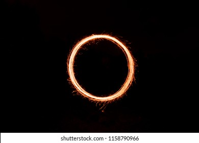 Round shape (circle) or letter O, painted with sparklers using long exposure technique on a dark background. Abstract, universal shape ideal for celebration designs.