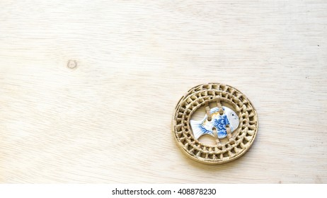 Round shape rattan weaved coaster with ceramic fish theme in the middle on a wooden surface. Slightly de-focused and close-up shot. Copy space.