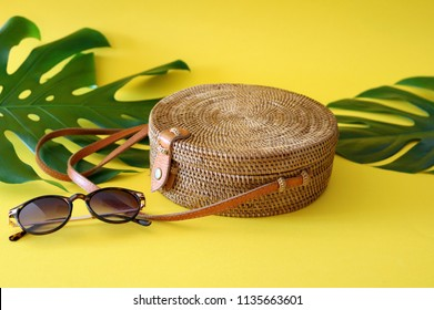 Round shaped Ata rattan boho bag with a leather strap laying on a Monstera leaf and yellow, sunny background with a pair of sunglasses next to it.