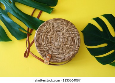 Round shaped Ata rattan boho bag with a leather strap laying on a Monstera leaf and yellow, sunny background.
