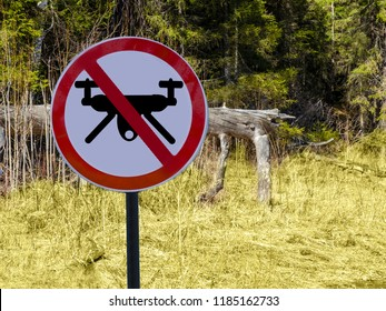 A round sign ban drones in the background of a Park or forest.